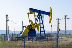 Presa blu e gialla della pompa sopra un pozzo di petrolio circondato dai pali di elettricità e protettivo con un recinto, nella  fotografia stock libera da diritti