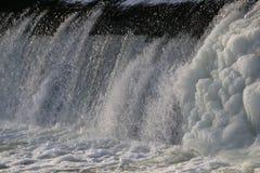 Presa, cascada la corriente del río cae de la presa en el invierno presa helada con una corriente fuerte del río descensos brilla Fotos de archivo libres de regalías