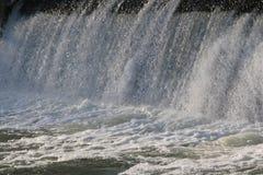 Presa, cascada la corriente del río cae de la presa en el invierno presa helada con una corriente fuerte del río descensos brilla Fotografía de archivo