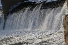 Presa, cascada la corriente del río cae de la presa en el invierno presa helada con una corriente fuerte del río descensos brilla Imagen de archivo libre de regalías