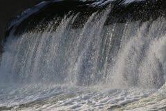 Presa, cascada la corriente del río cae de la presa en el invierno presa helada con una corriente fuerte del río descensos brilla Imágenes de archivo libres de regalías