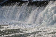 Presa, cascada la corriente del río cae de la presa en el invierno presa helada con una corriente fuerte del río descensos brilla Imagen de archivo