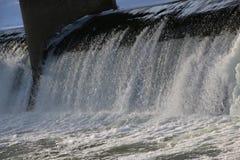 Presa, cascada la corriente del río cae de la presa en el invierno presa helada con una corriente fuerte del río descensos brilla Fotos de archivo