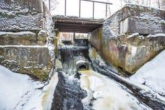 Presa concreta del río con la corriente de no-congelación del agua en invierno Fotos de archivo libres de regalías