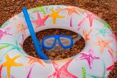 Presa d'aria subacquea della maschera del bambino dei sandali gonfiabili del cerchio, bugia sulla spiaggia fotografia stock