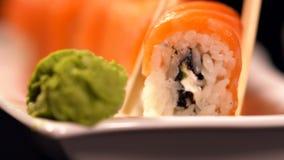 Presa dei sushi di maki di California con i bastoncini video d archivio