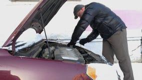 Presa del meccanico dell'uomo della batteria scaricata dall'automobile stock footage