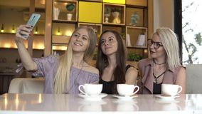 Presa dell'autoritratto Tre amici femminili che fanno autoritratto mentre pausa caffè archivi video