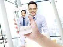 Presa dell'immagine di un uomo d'affari con il telefono cellulare fotografia stock