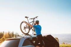 Presa dell'uomo del ciclista in mountain-bike della sua bici dal tetto dell'automobile fotografia stock