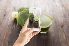 Presa della foto del succo dei broccoli sulla tavola di legno Immagine Stock Libera da Diritti