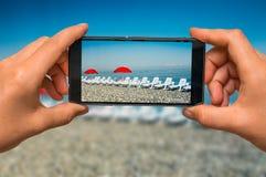 Presa della foto delle chaise-lounge del sole e degli ombrelli rossi con il telefono cellulare Fotografie Stock Libere da Diritti