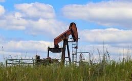 Presa di lavoro arancio della pompa su olio o pozzo di gas sull'orizzonte del campo verde con la brocca di prodotti chimici che s Immagini Stock