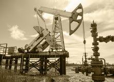 Presa e testa di pozzo della pompa nel giacimento di petrolio Immagini Stock