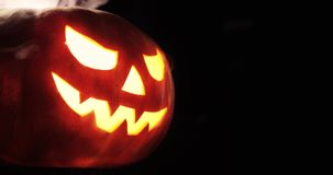 Presa-o-lanterna brillante Zucca di Halloween con il fumo spaventoso del fronte dentro con la fiamma isolata sui precedenti neri video d archivio