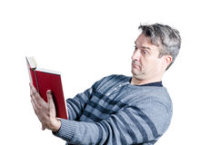 Presbyopia. Guy finding holding a book at quite a distance to be able to read Stock Image
