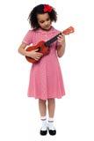 Preschool śliczna dziewczyna bawić się gitarę Obrazy Royalty Free