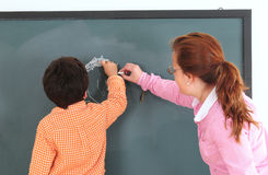 Preschool. Teacher with her preschooler writing on a chalkboard Royalty Free Stock Images
