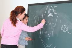 Preschool. Teacher with her preschooler writing on a chalkboard Stock Photo