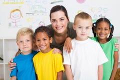 Preschool. A happy preschool class posing with their teacher in classroom Stock Photos