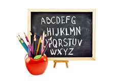 Preschool. Preschool still life of a blackboard and some colorful pencils in apple-shaped stand, isolated on white Royalty Free Stock Images