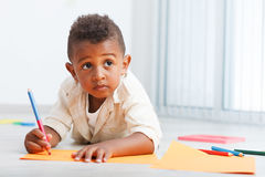 Preschool african child. Preschool child boy drawing on the floor Royalty Free Stock Image