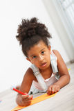 Preschool african child. Preschool child girl drawing on the floor Royalty Free Stock Photo