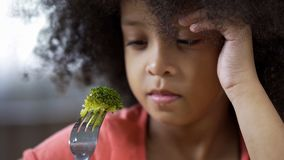 Preschool African girl sadly looking at piece of broccoli on, healthy nutrition