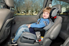 Preschool age boy in a booster seat. Boy in a booster seat in the back of a van Stock Image