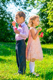 Preschool age children with soap bubbles. Outdoors royalty free stock images