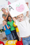 Preschool art. A happy young boy showing off his preschool art in classroom with teachers and classmates cheering him on in background Stock Images