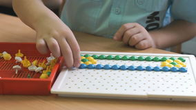 Preschool boy collects figure using colored chips stock video footage