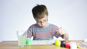 Preschool boy draws a picture of a paintbrush stock footage
