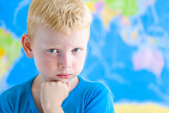 Preschool boy dreaming in fron of  world map. Cute preschool boy dreaming in fron of  world map Stock Image