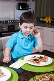 A preschool boy eat pizza in kitchen Stock Images