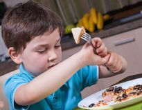 Preschool boy eat pizza in the kitchen Royalty Free Stock Photography