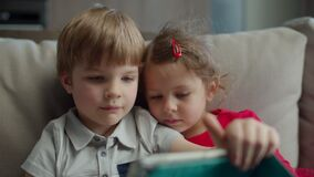 Preschool boy and girl using tablet computer sitting on couch at home. Kids using mobile application on tablet computer