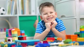 Preschool boy is playing with different colorful toy bricks in a kindergarten. Preschool boy is playing with different colorful toy bricks in a childcare. He is stock video footage