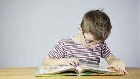 Preschool boy reading a book stock footage