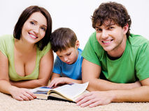 Preschool boy reading book with his  parents Royalty Free Stock Images