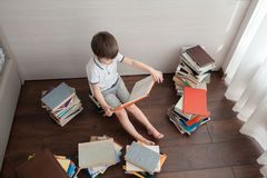 A preschool boy is sitting on books. A preschool boy is sitting on books and holding a large open book. View from above royalty free stock image
