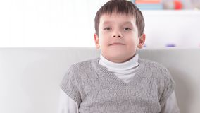 Preschool boy sitting on the couch in the nursery.  royalty free stock photography