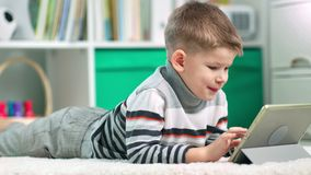 A preschool boy is surfing the internet with his tablet computer. He is studying or playing video games stock video