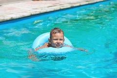 Preschool boy swims in pool Stock Images
