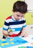 A preschool boy use glue for homework Stock Image