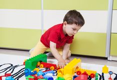 Preschool boy who build towers with plastic cubes Stock Photos