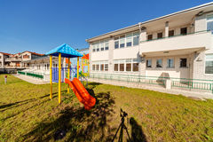 Preschool building. Exterior with playground on a sunny day royalty free stock image