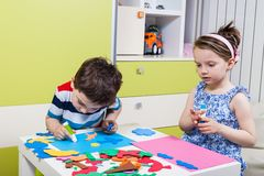 Preschool child create a picture with foam shapes. Two preschool child create a picture with foam shapes Stock Photography
