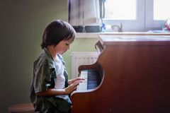 Preschool child, cute boy, playing piano at home Royalty Free Stock Photography