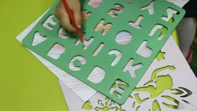 Preschool child learning. Preschool child during educational activities - drawing letters using template stock footage